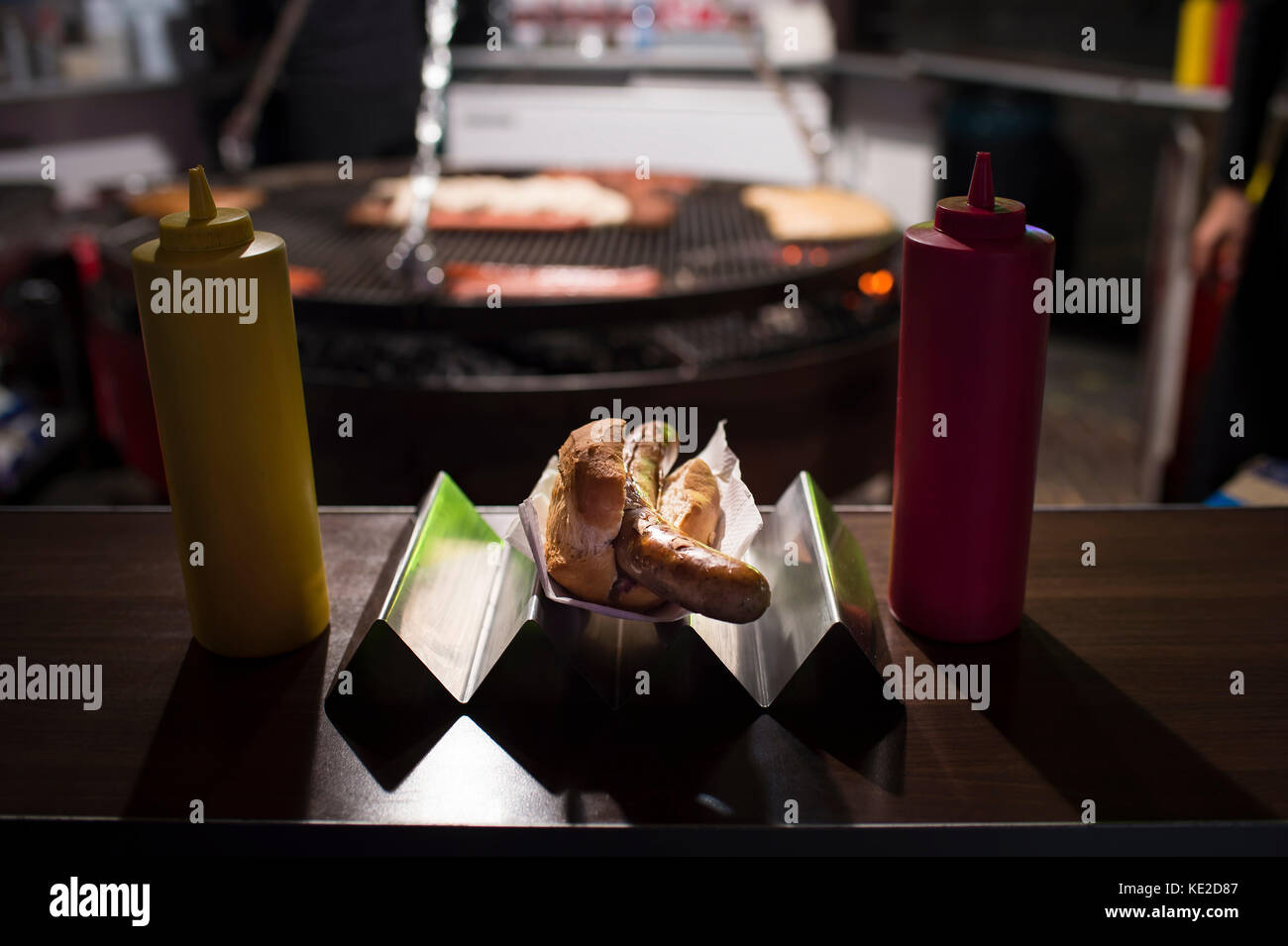 Sausage in the bread roll in the evening in the sausage stand - Stock Image