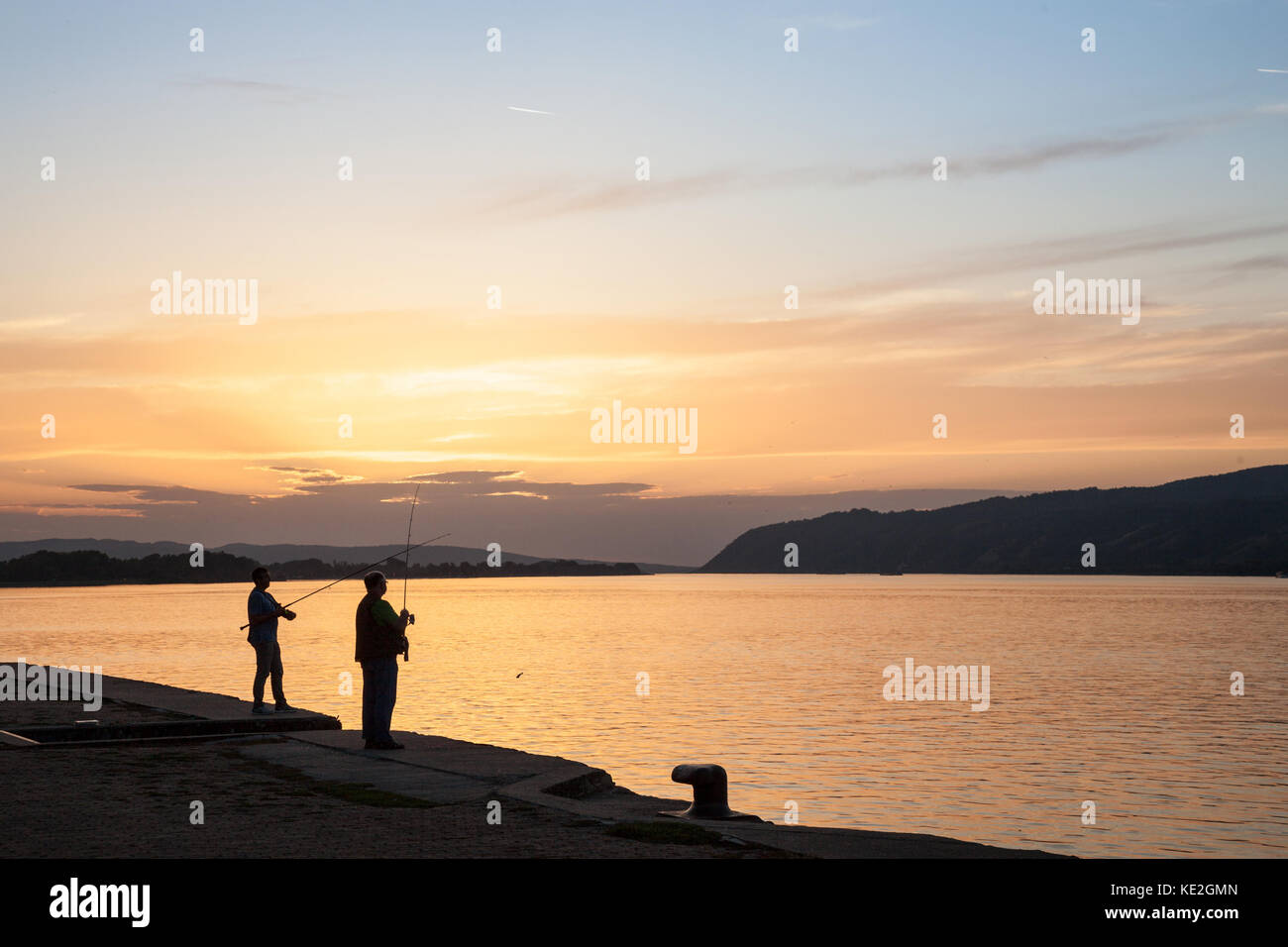 VELIKO GRADISTE, SERBIA - SEPTEMBER 16, 2017: Fishermen fishing on the quay of Veliko Gradiste at Sunset on the - Stock Image