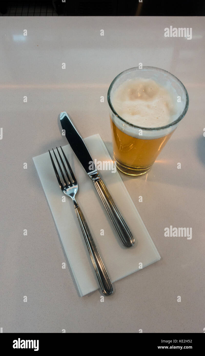 A pint of draft beer, knife and fork and napkin - Stock Image