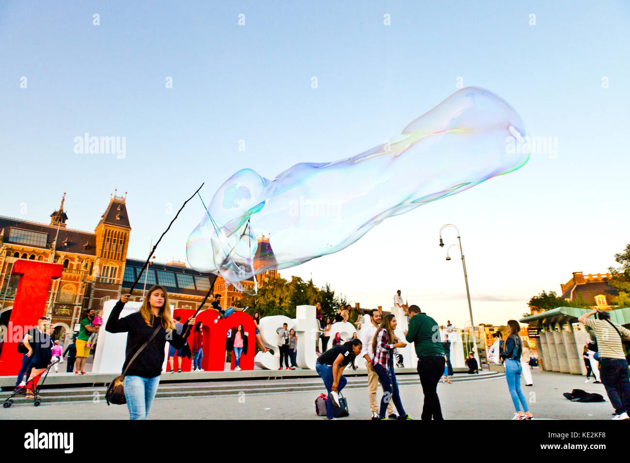 A street performer creates a giant soap bubble near the I Amsterdam logo on the Museumplein in Amsterdam - Stock Image