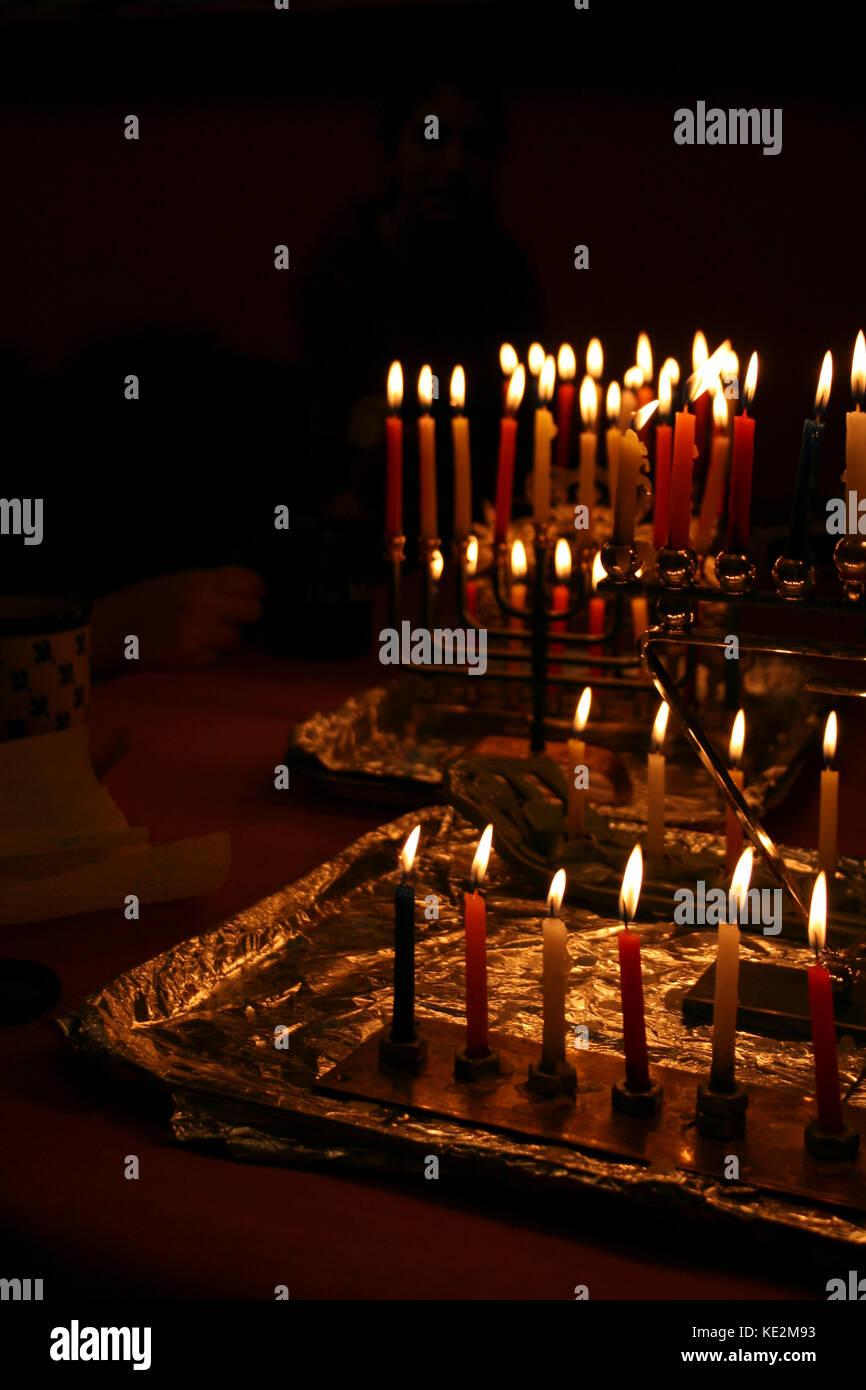 Chanuka / Hanuka candles burning in hanukiya s / hanukiyot during the Jewish festival of Chanuka / Hanuka. Candle - Stock Image