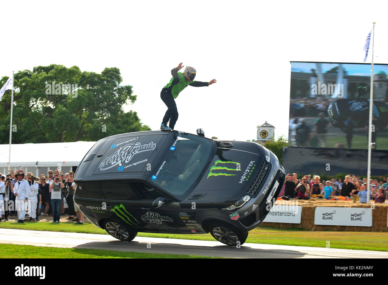 A stunt driver stands on top of a moving car at the 2017 Goodwood Festival of Speed. Stock Photo