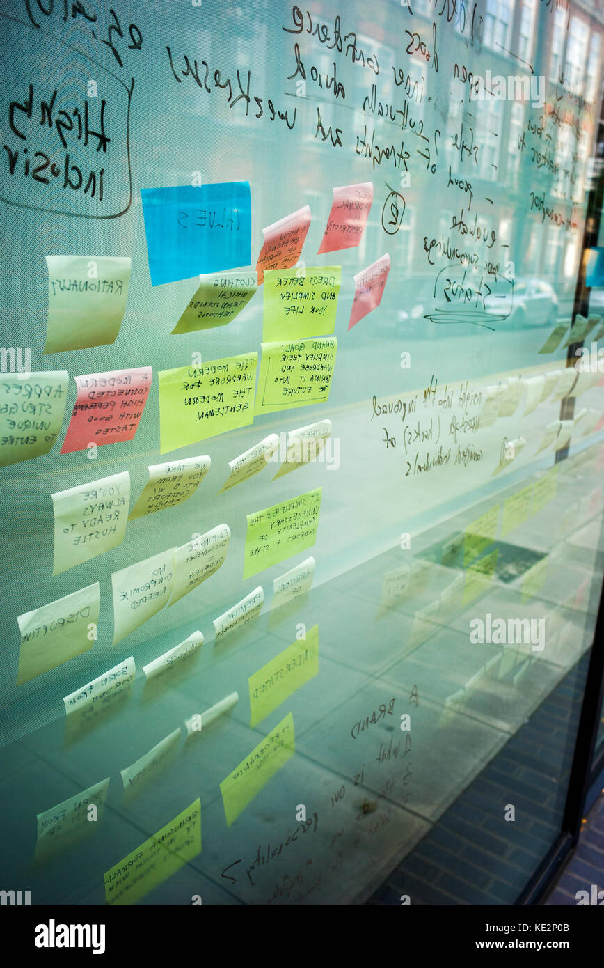 post it notes stuck to window with brainstorming annotations written on them clearly visible - Stock Image