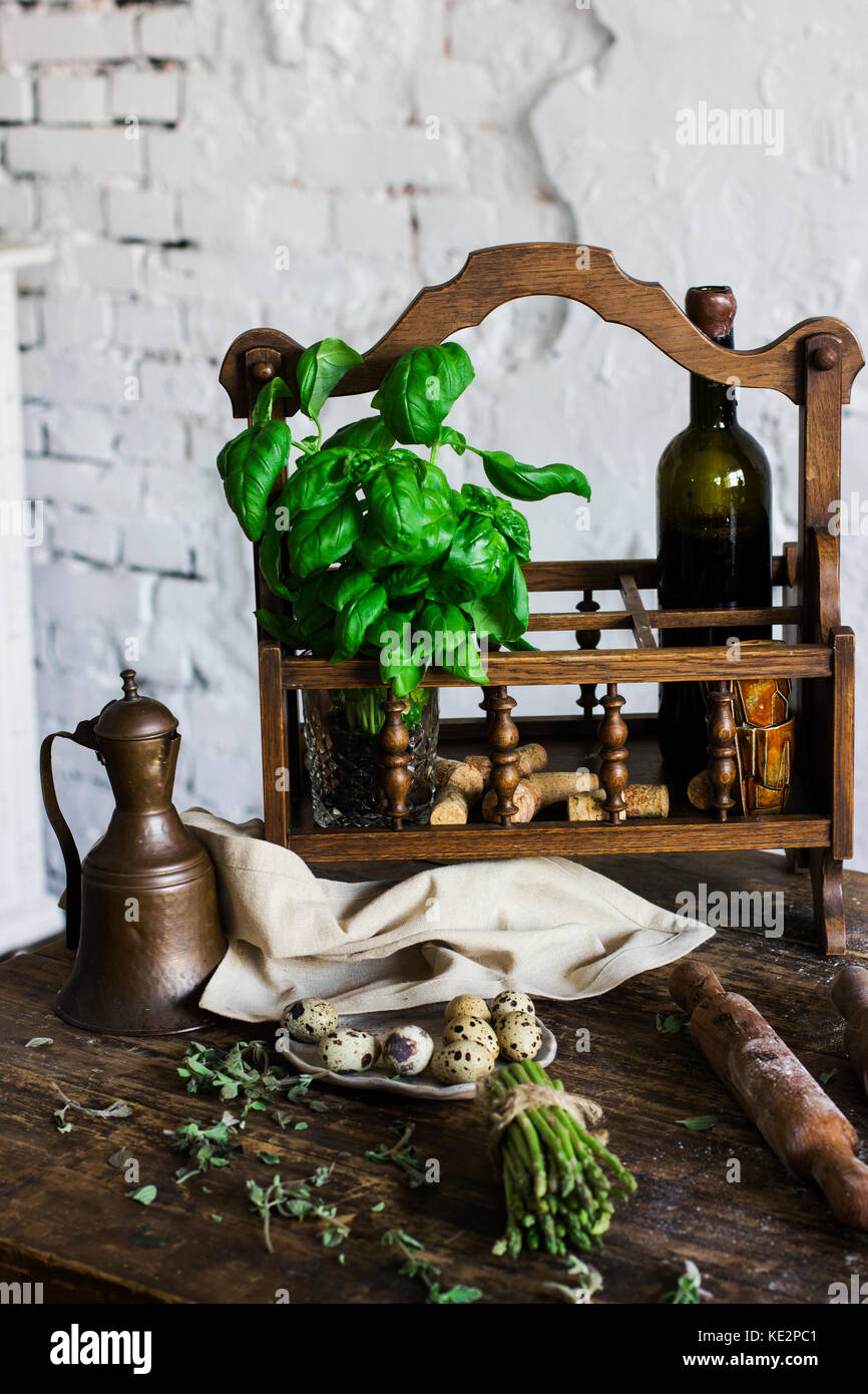 The bottle of wine, Basil and ingredients for cooking in rustic kitchen - Stock Image