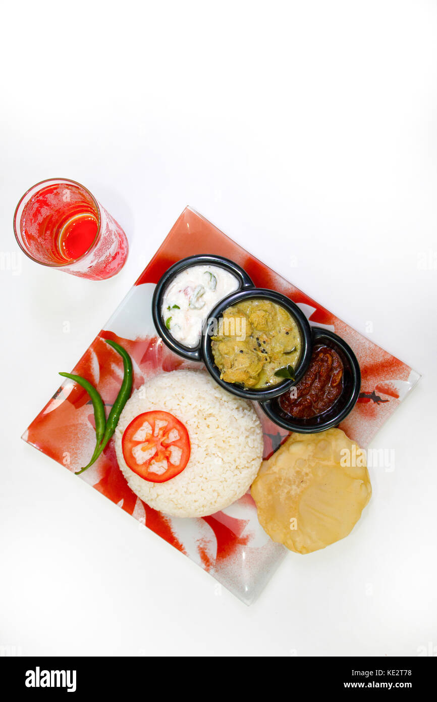 Indian Gee rice with complete curry meal served on a tray in a restaurant and glass of water top view - Stock Image