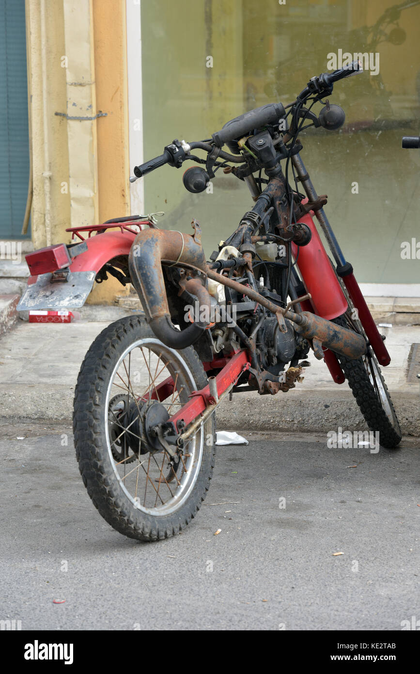 an abandoned wrecked and broken down motorcycle left and forgotten in a greek street in kerira, corfu, Greece. - Stock Image