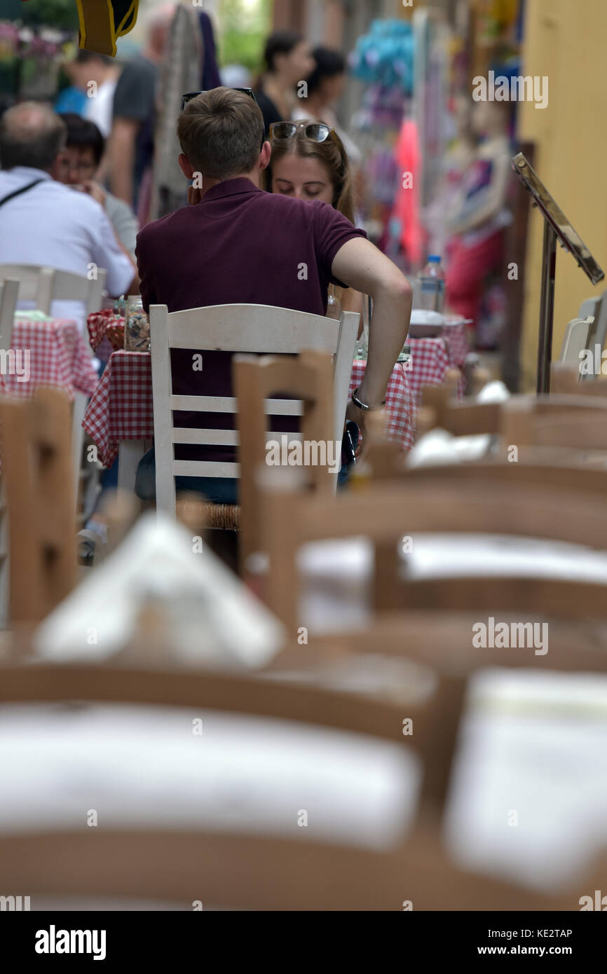 a young couple eating at a typical greek tavern in a crowded street in the old town of Kerkira on corfu in Greece - Stock Image