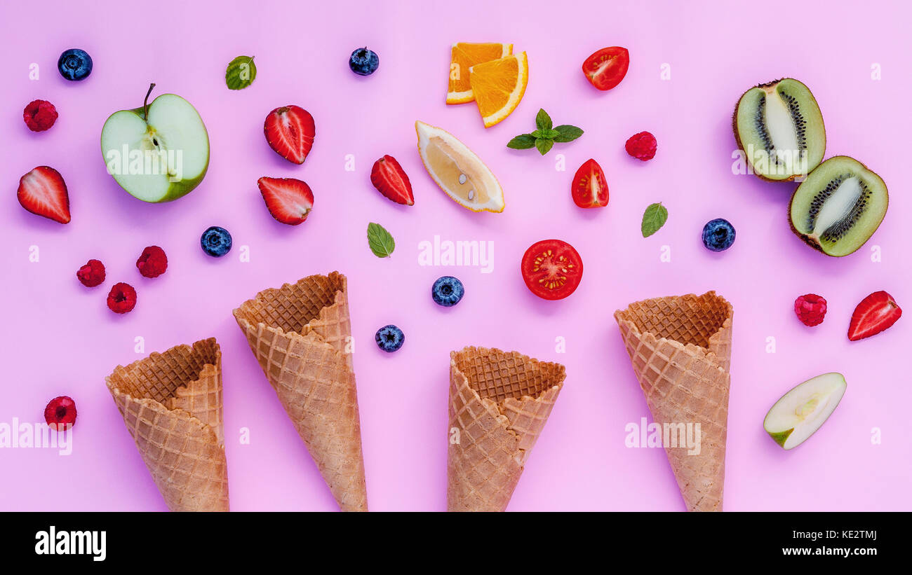 Cones and colorful various fruits raspberry ,blueberry ,strawberry ,orange slice , halved kiwi ,apple,tomato and - Stock Image