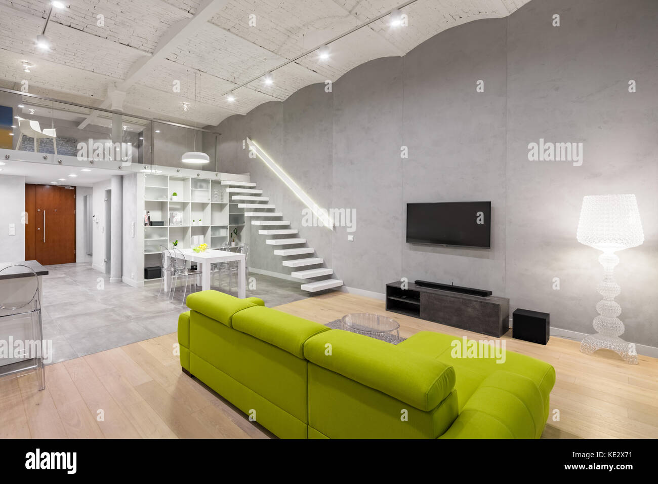 Home interior with green couch, tv and mezzanine - Stock Image