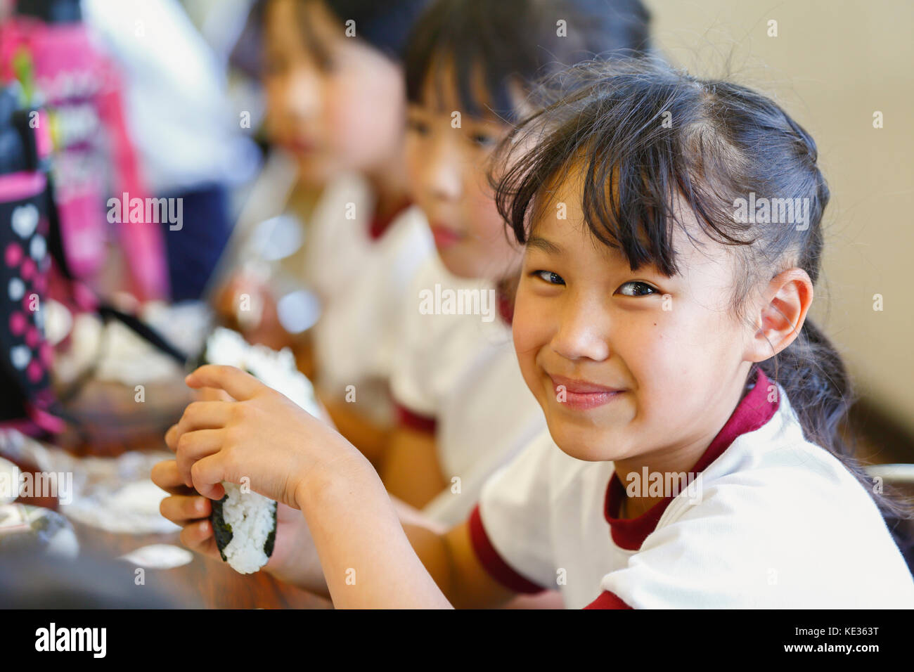 Japanese elementary school kids eating in the classroom - Stock Image