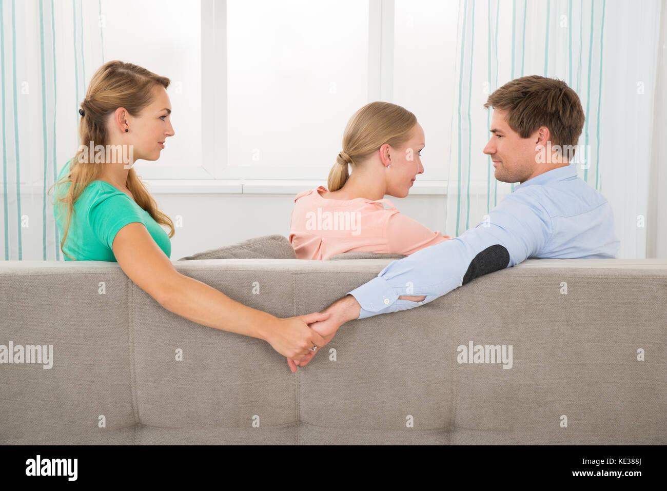 Love triangle. Young Man Sitting On Sofa Holding Hands Of His Female Friend While Looking At Girlfriend - Stock Image