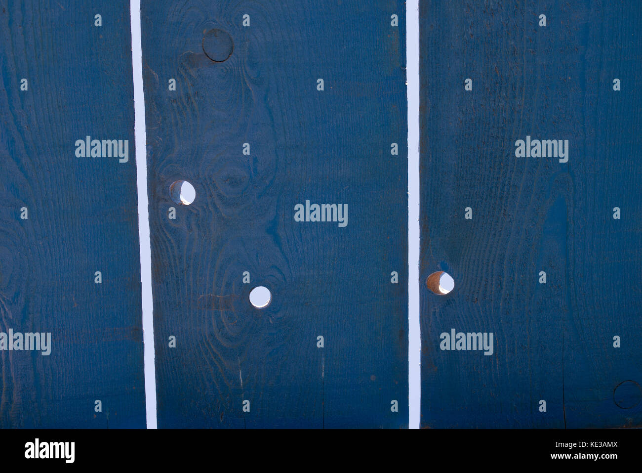 light holes through wooden dark blue planks - Stock Image