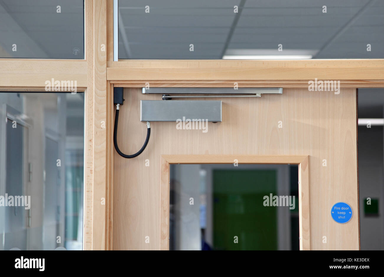 Close-up of an electronically operated, magnetic fire door closer on interior doors in a UK college building. - Stock Image