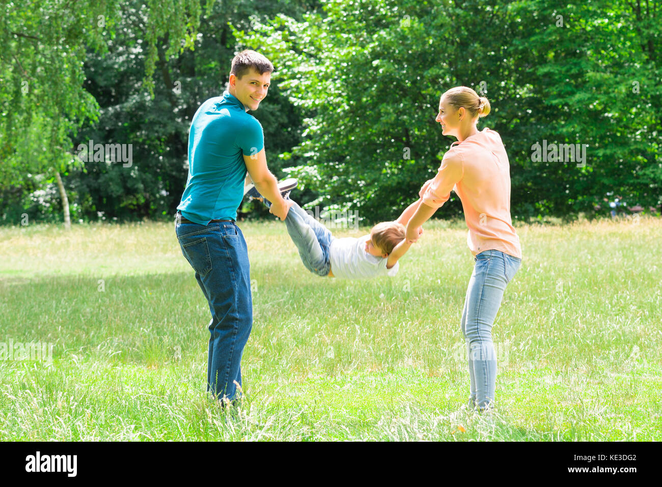 Smiling Young Parent Swinging Their Son In The Park - Stock Image