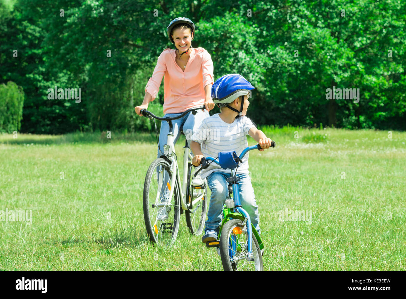 Mother And Son Enjoying The Ride On Bicycle In The Park Stock Photo