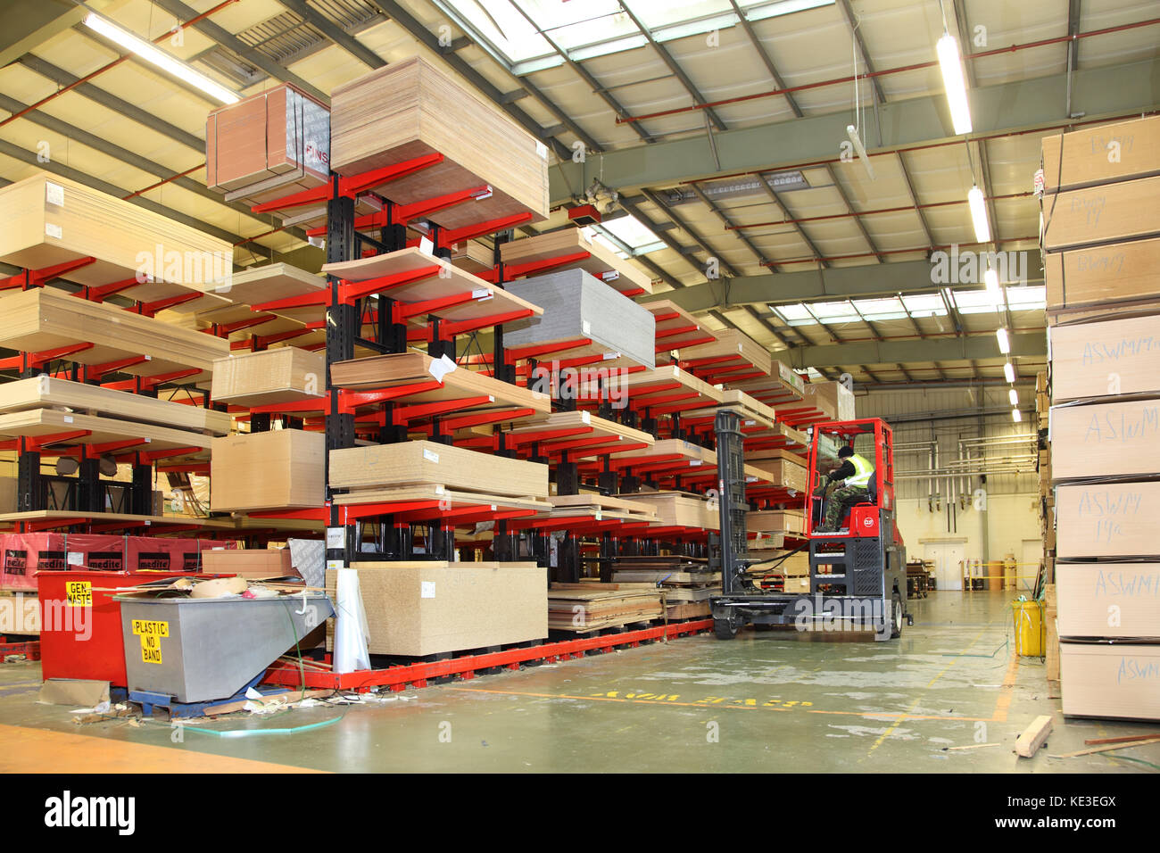 A fork lift truck removes timber sheet products stacked in a modern, UK distribution warehouse. - Stock Image