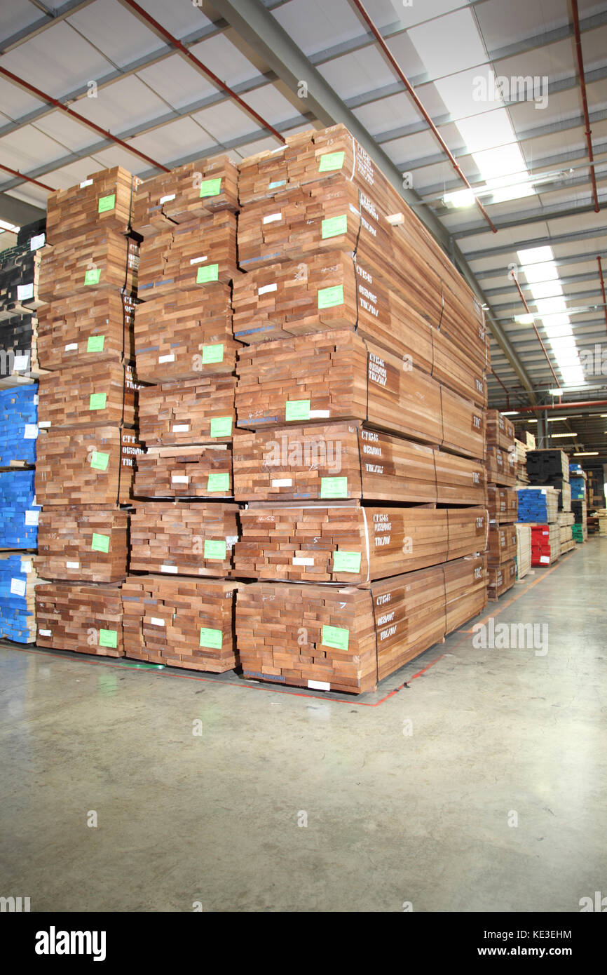 Imported hardwood timber planks stacked in a modern, UK distribution warehouse. - Stock Image