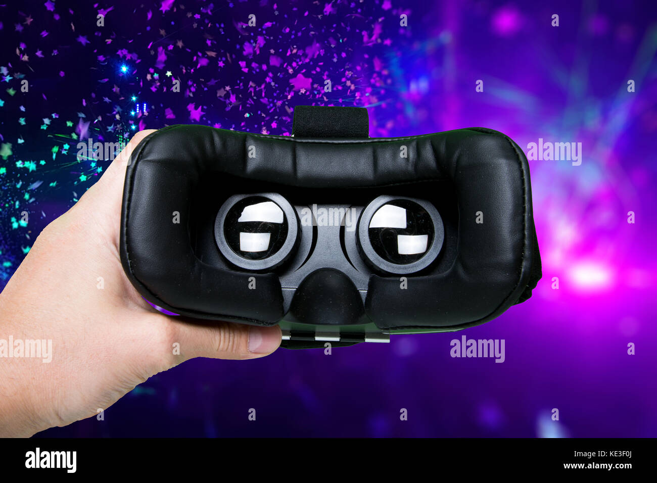 Man hand holding VR glasses on colorful background Top view/Hands of