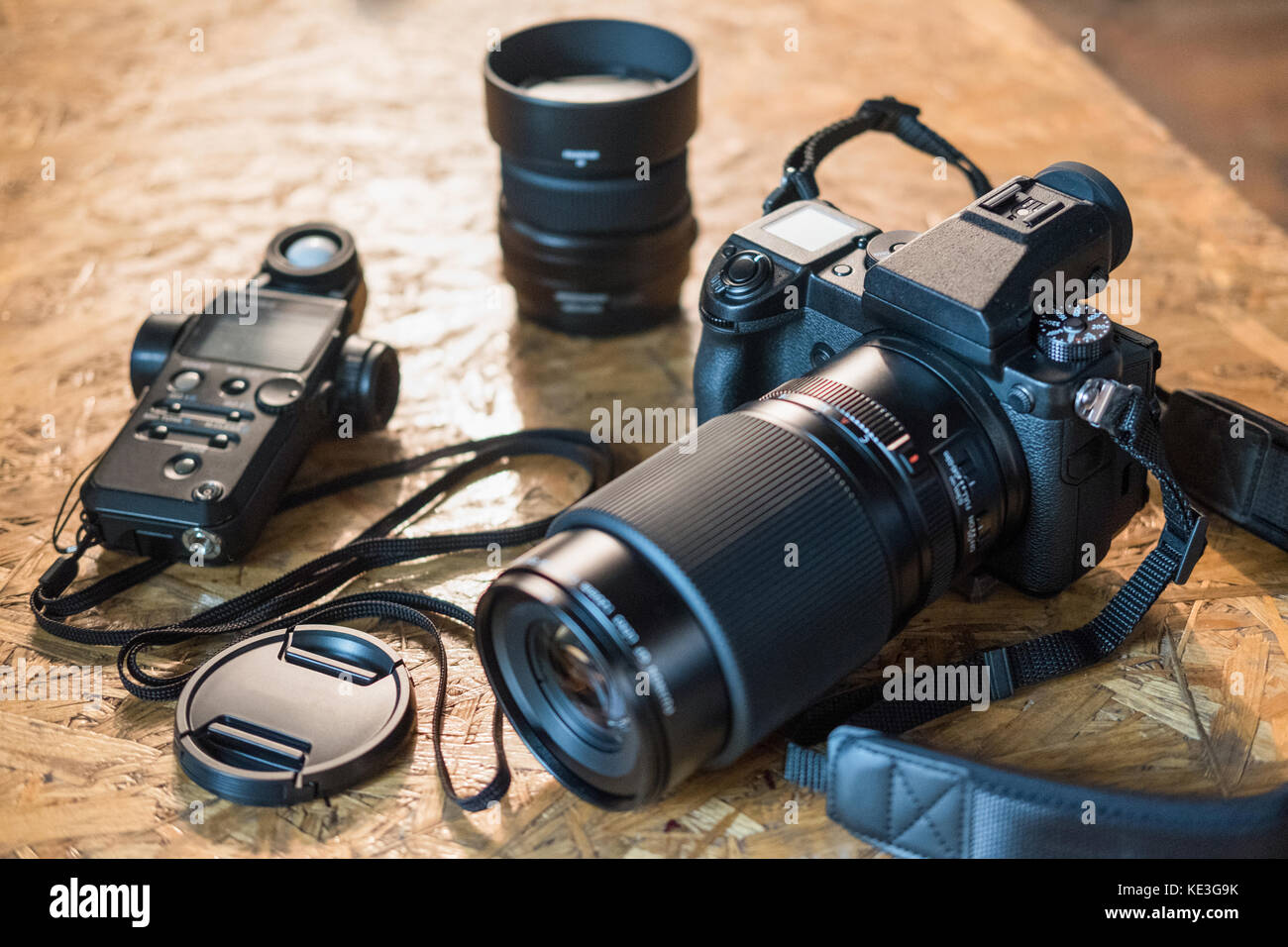 photo equipment and camera on a wooden table close-up. modern digital camera - Stock Image