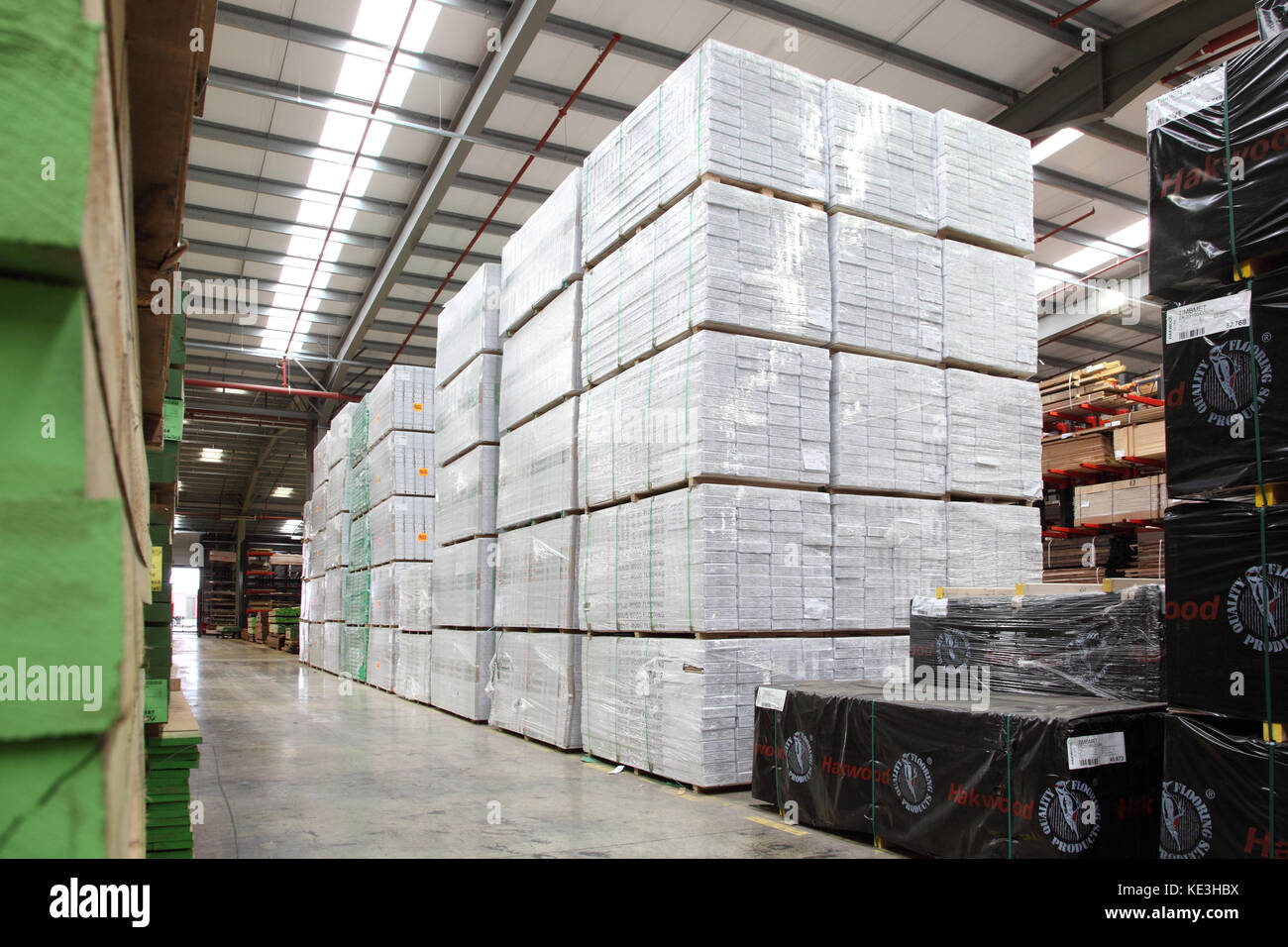 Imported timber planks and sheet products stacked in a modern, UK distribution warehouse. - Stock Image