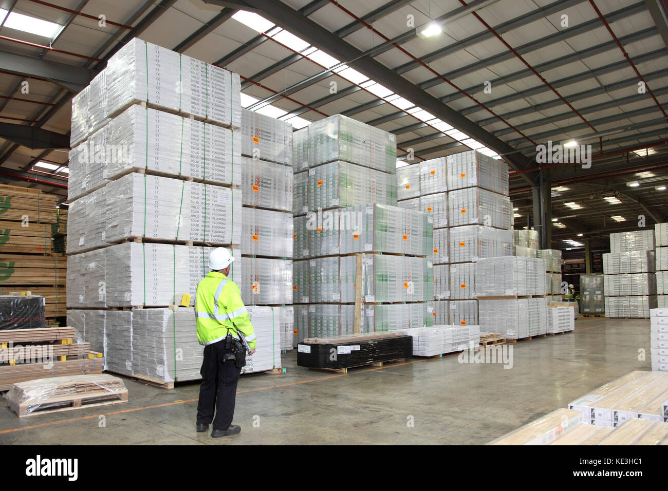 Shrink-wrapped packs of timber flooring and sheet products stacked in a modern, UK distribution warehouse. - Stock Image