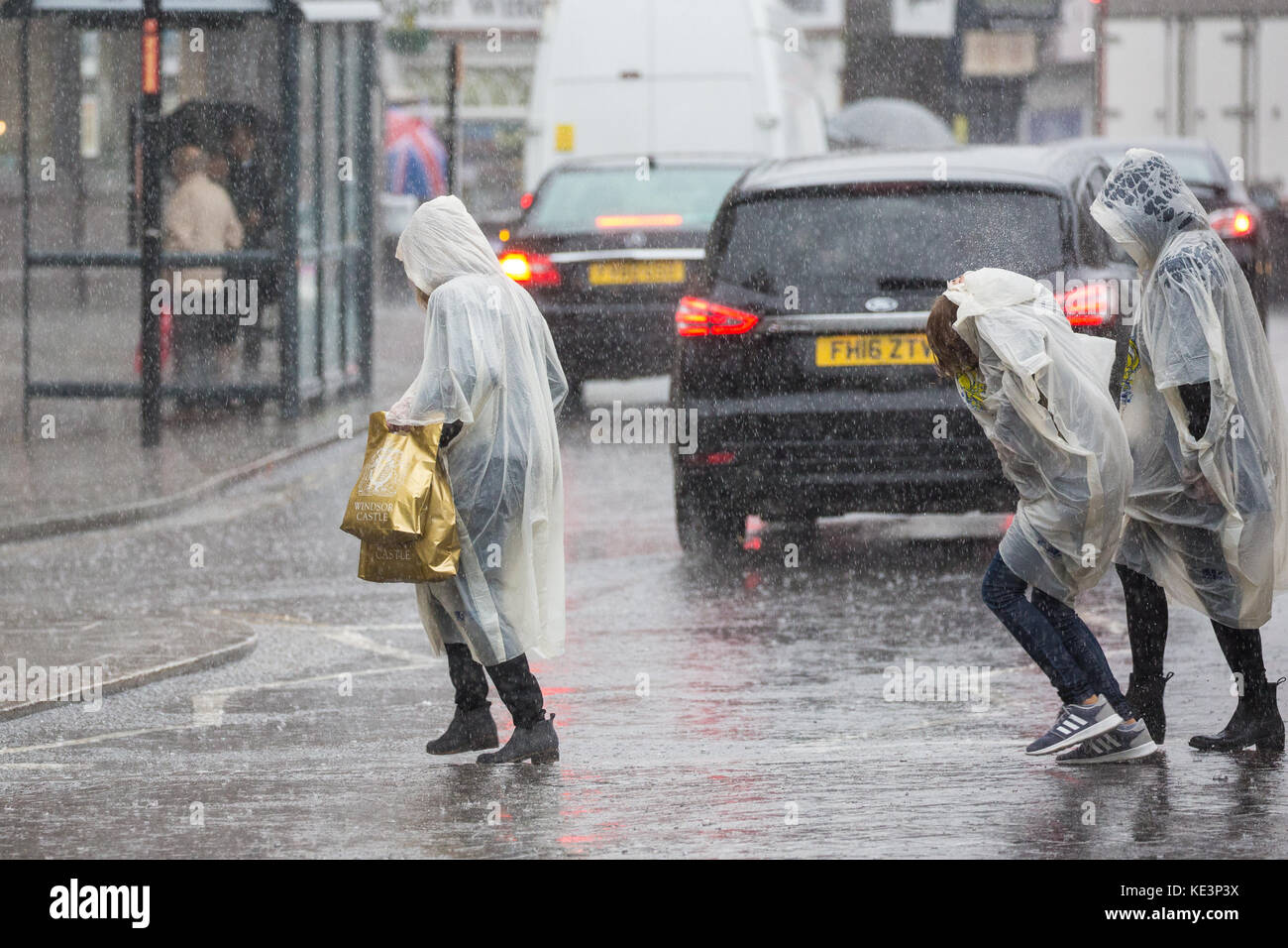 Windsor, UK. 18th Oct, 2017. Tourists wearing foldaway ponchos leave Windsor Castle during a sudden downpour. The - Stock Image
