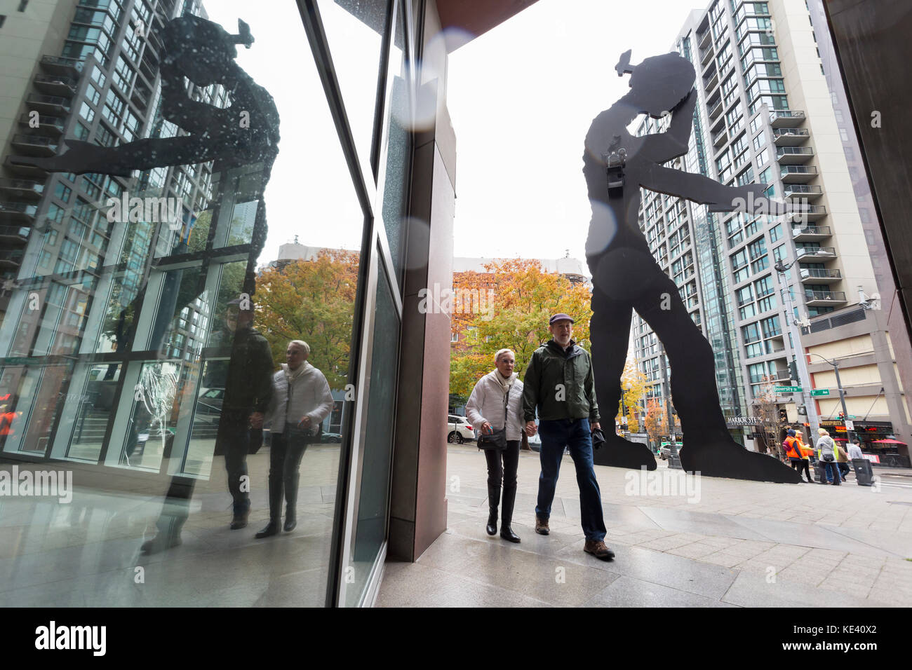 Seattle, United States. 18th Oct, 2017. Seattle, Washington: Couple walks by the Hammering Man at the Seattle Art Stock Photo