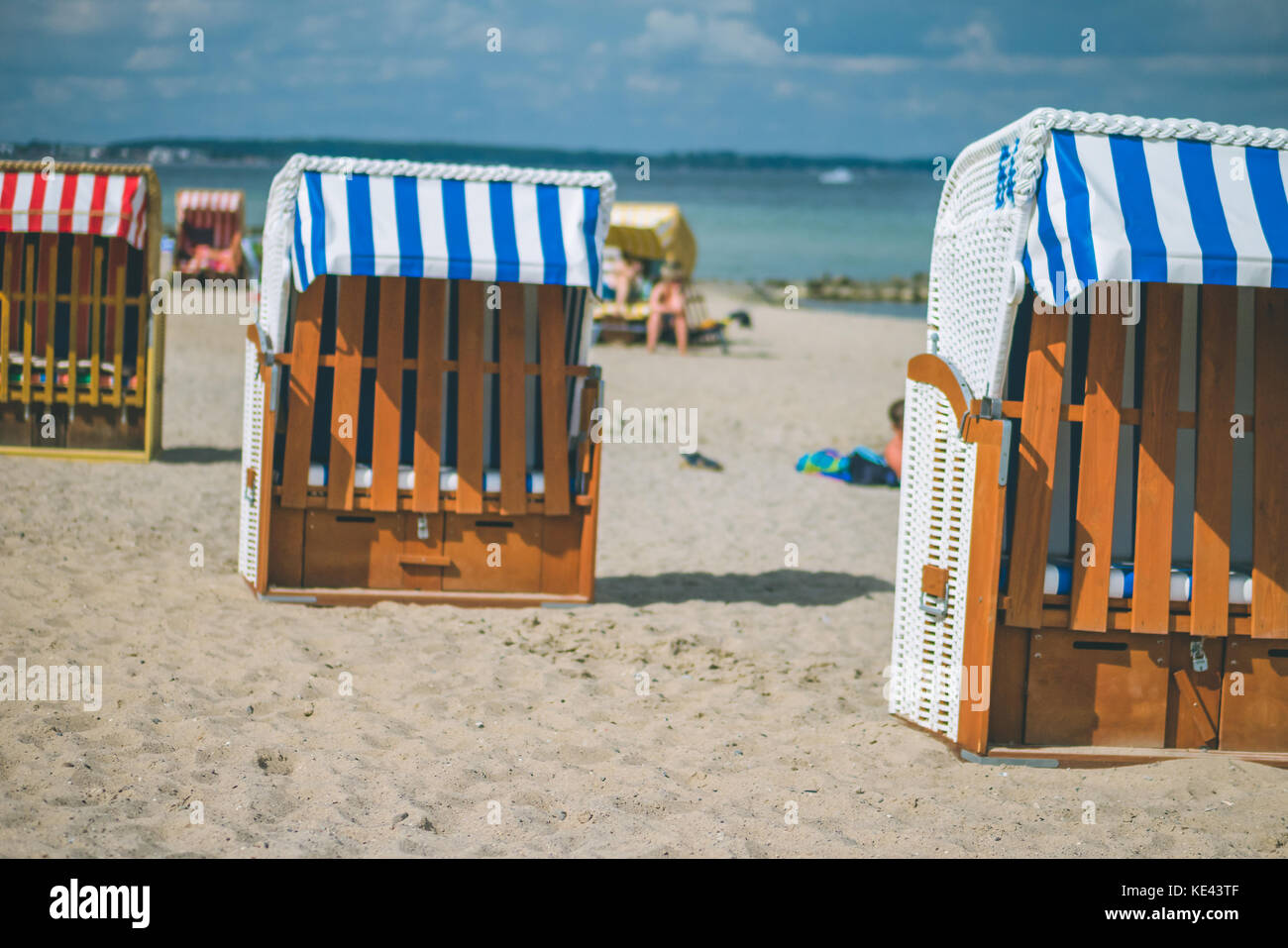 Colorfuled striped roofed chairs on sandy beach in Travemunde. A blurred couple sitting on beach in background. - Stock Image
