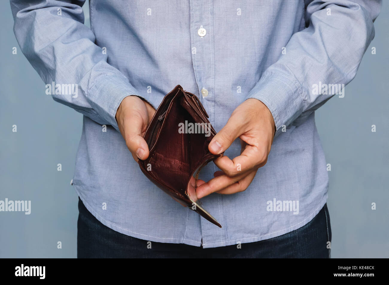 Bankruptcy - Business Person holding an empty wallet. Man showing empty wallet by showing the inconsistency and Stock Photo