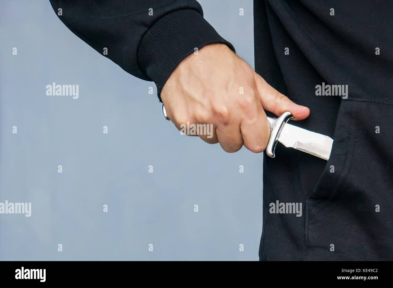 Hand from the pocket of the black jacket pulls out a folding knife close up. Extortion and intimidation. The concept - Stock Image