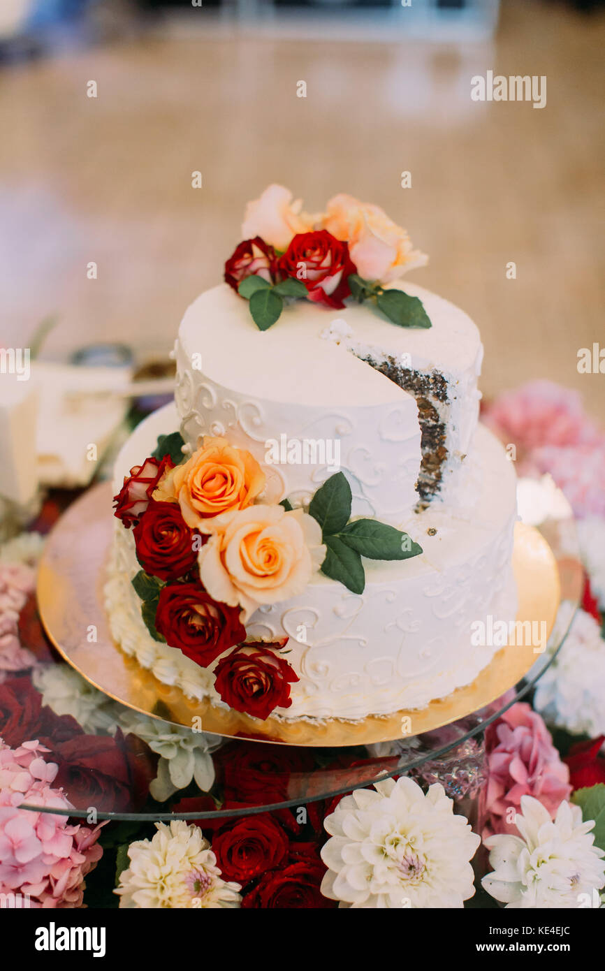 Close-up view of the wedding cake decorated with colourful roses. - Stock Image