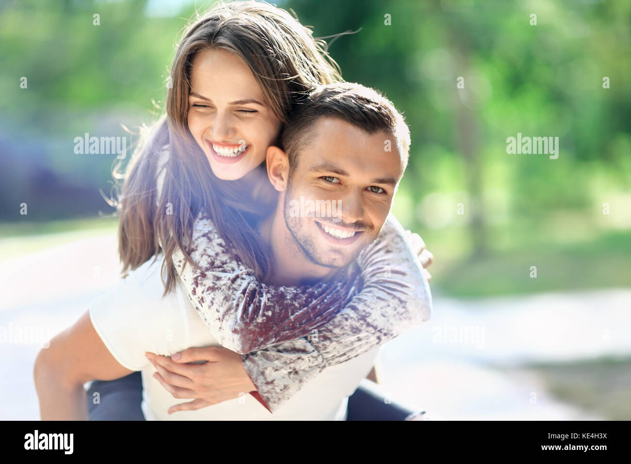 Man carrying his girlfriend on the back. Happy laughing couple piggyback. Young cheerful loving pair have fun together - Stock Image