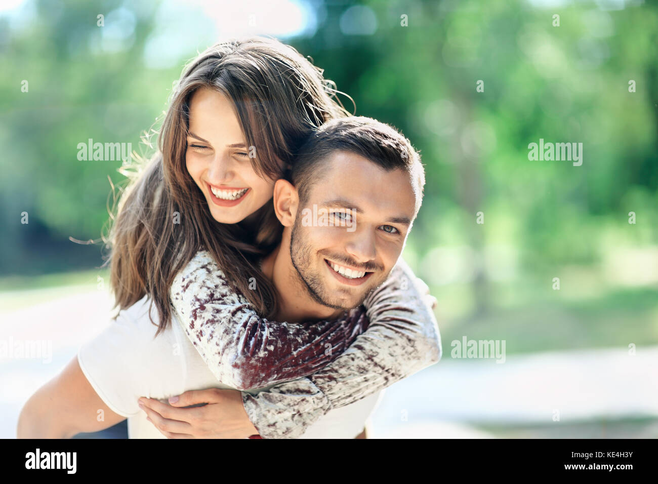 Outdoors portrait of lovers happy young man and woman looking at camera. Smiling girl piggyback of her boyfriend. - Stock Image
