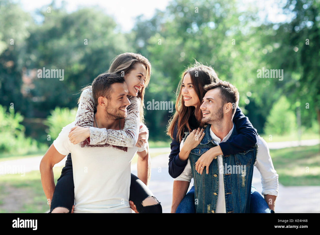 Two loving couples piggyback having fun outdoors. Girls sitting on back of guys smiling. Young women and men playing - Stock Image