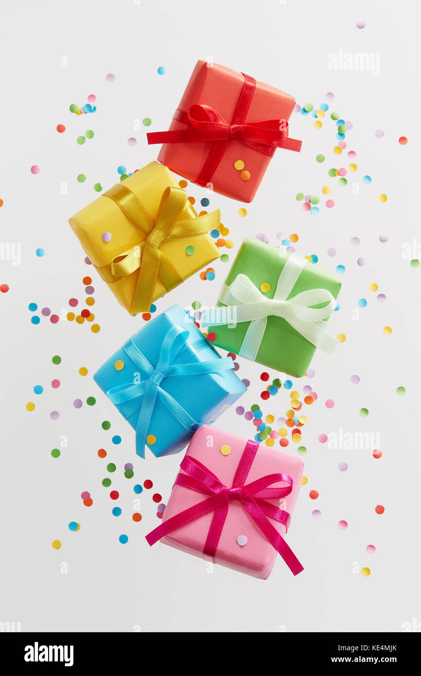 Colorful gift boxes with confetti falling or flying in motion. - Stock Image