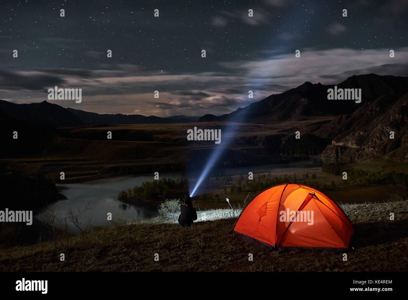 Man tourist with flashlight near his camp tent at night. Stock Photo