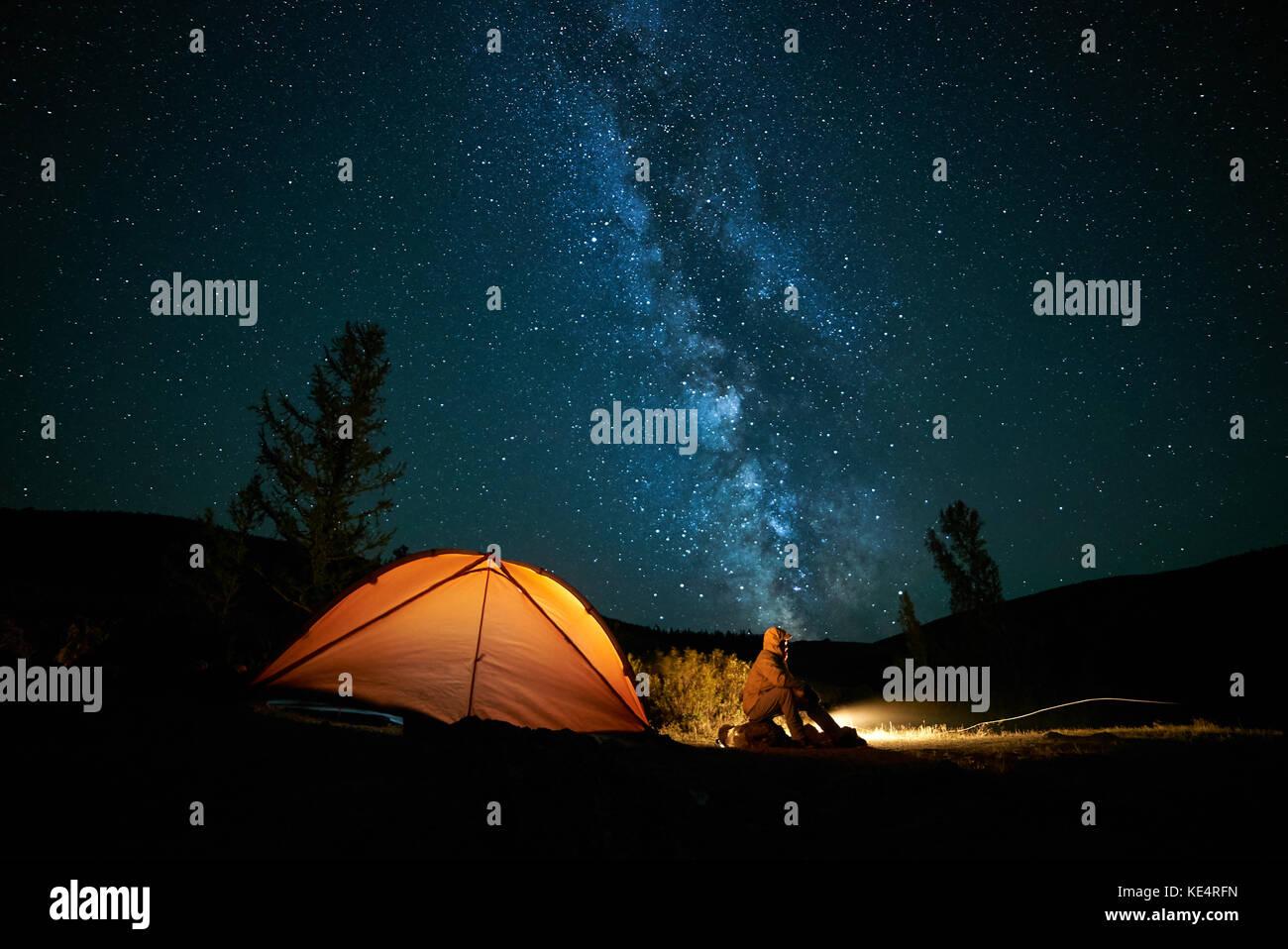 Man tourist near his camp tent at night. Stock Photo