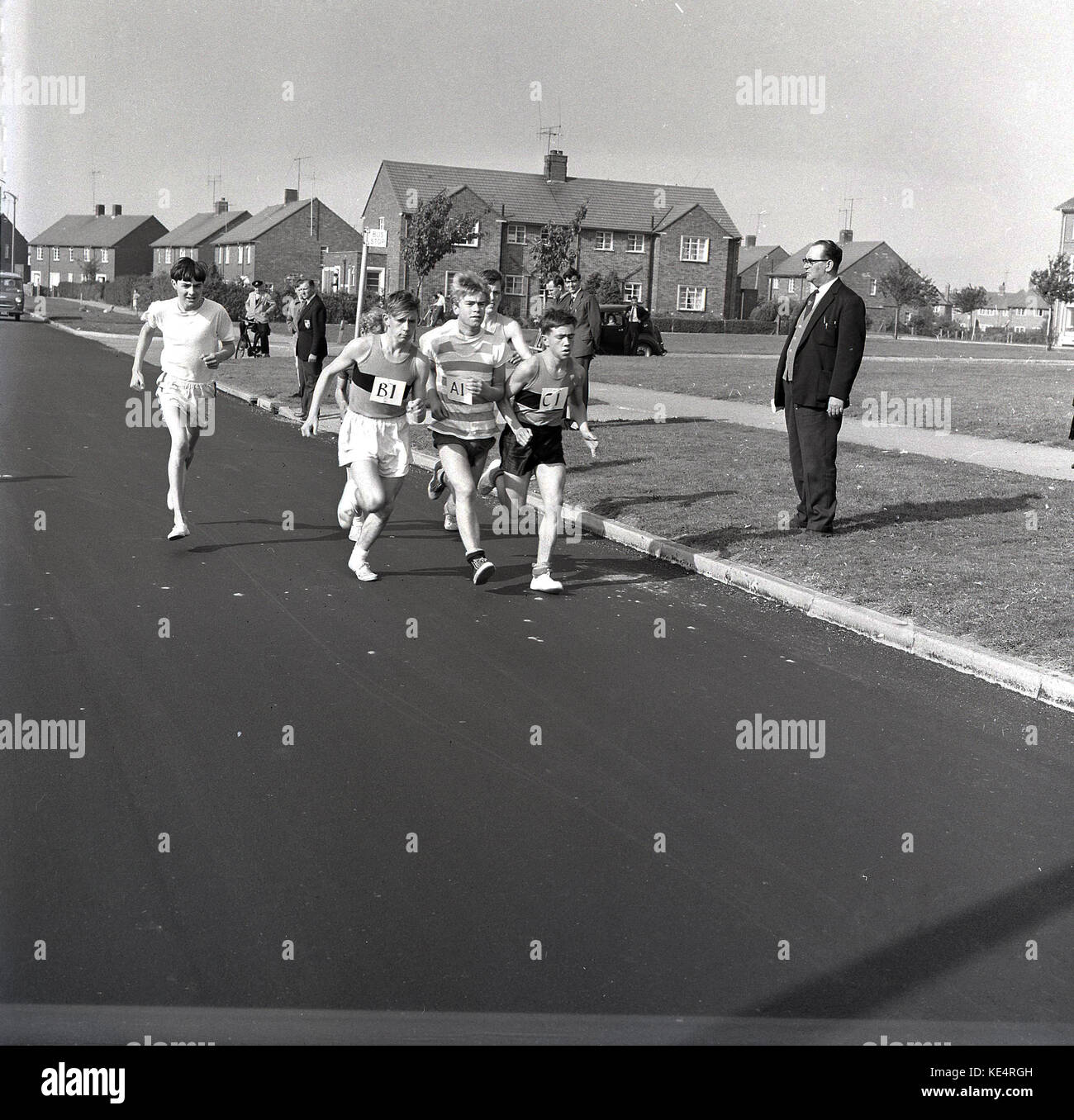1964, historical, group of teenage boys wearing vests and t-shirts and simple pilmsolls on their feet competiting - Stock Image