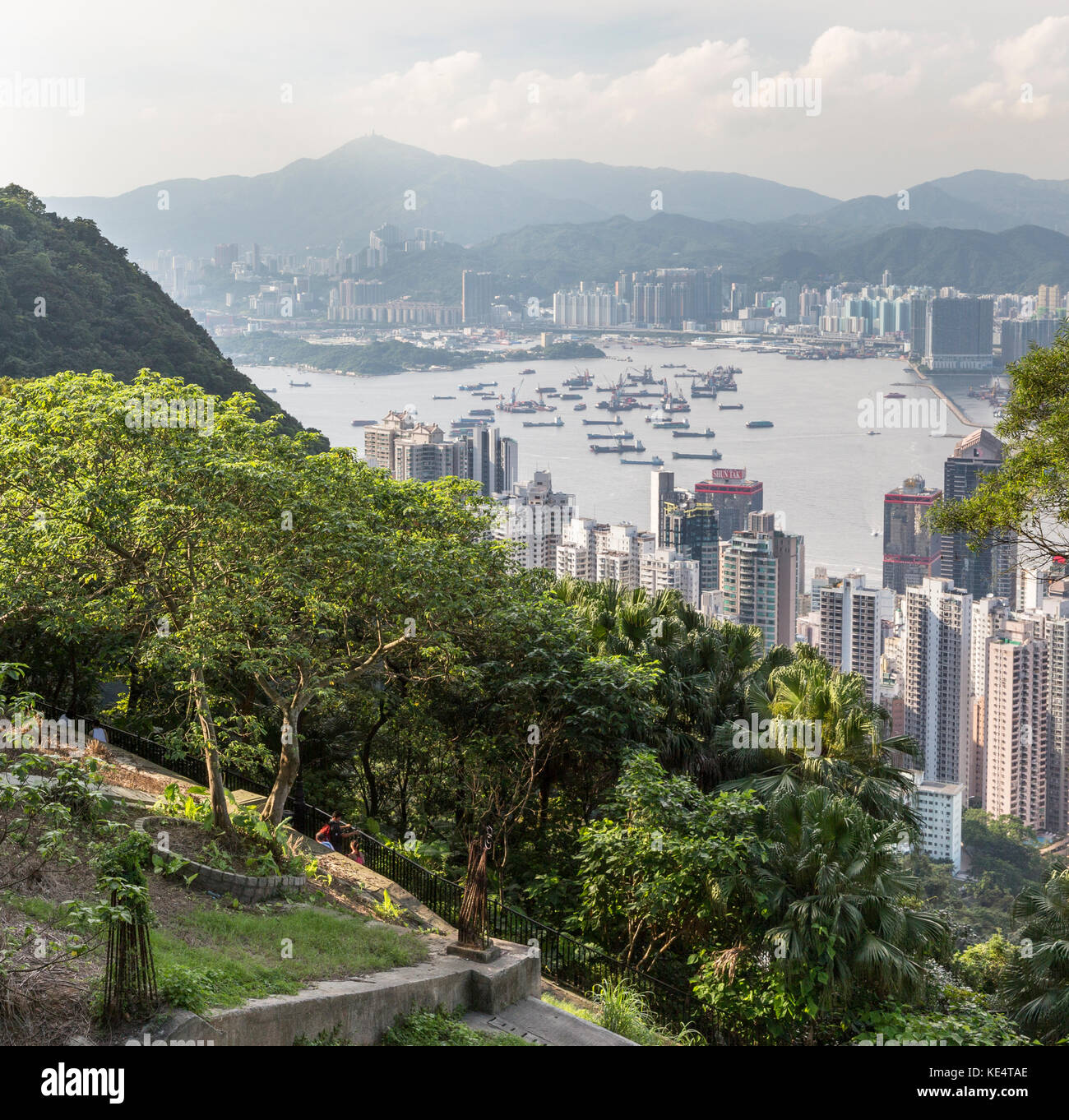 Hong Kong, SAR, China - 2 June 2013: Tourists on pathway at Victoria Peak with Victoria Harbour beyond - Stock Image