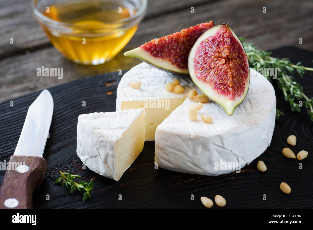 Camembert cheese with figs, honey and pine nuts on dark wooden cutting board. Closeup view - Stock Image