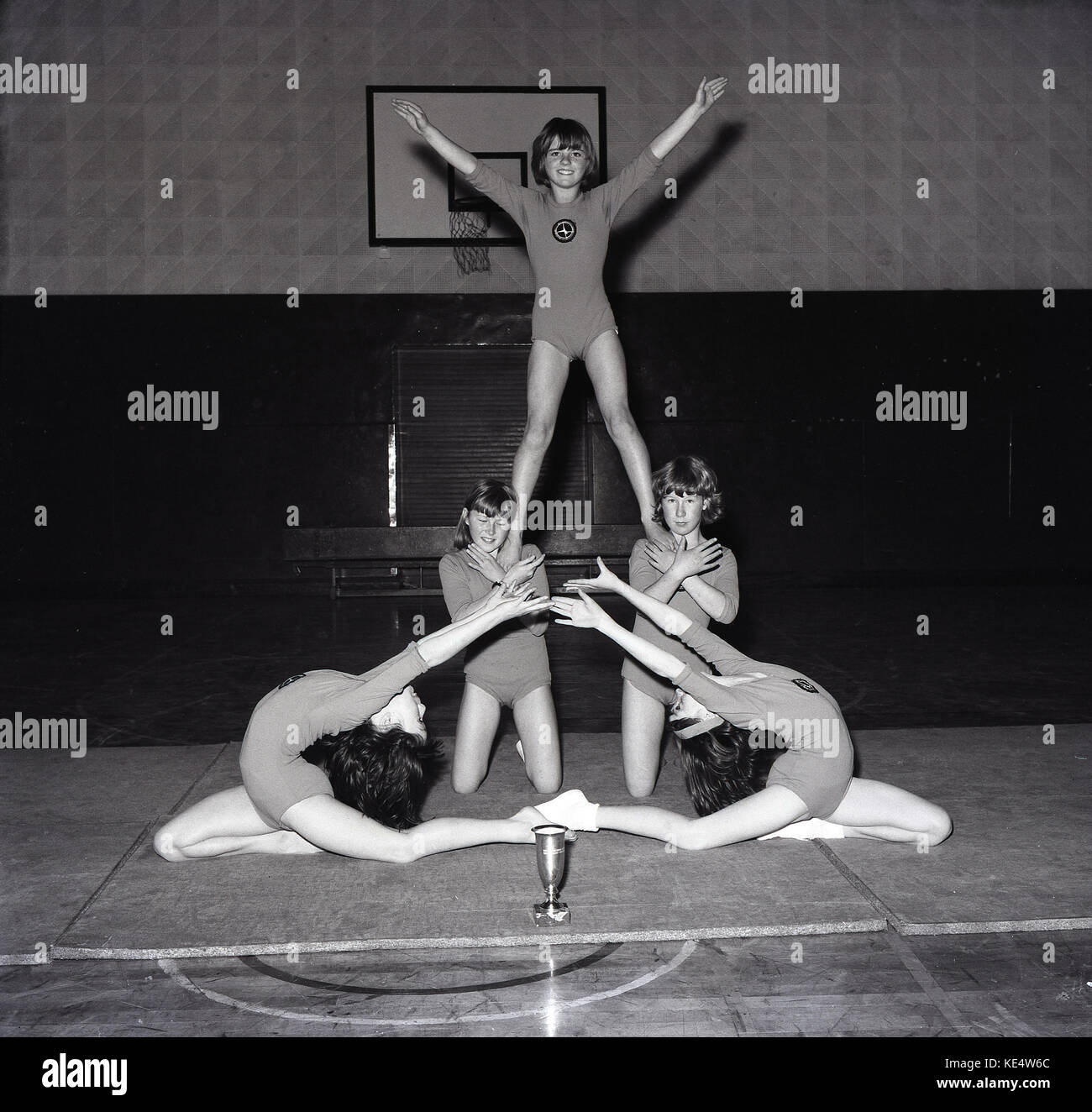 1960s, a picture from the mid-sixties of five young female artistic gymnasts showing off their talents in the school - Stock Image