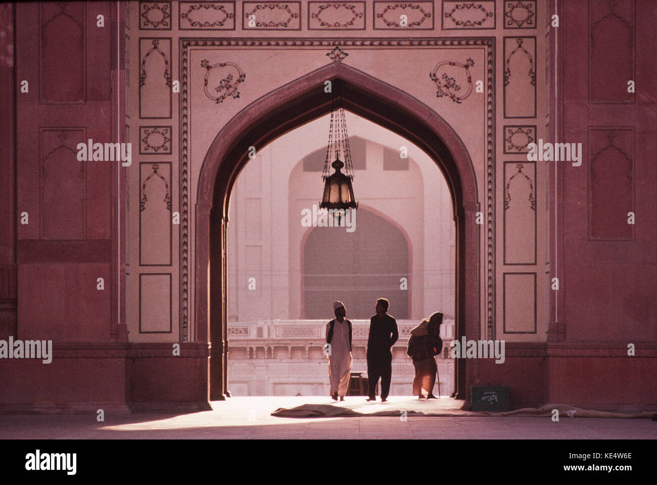 People coming through the main entrance to the Badshahi Mosque, Lahore, Pakistan. - Stock Image