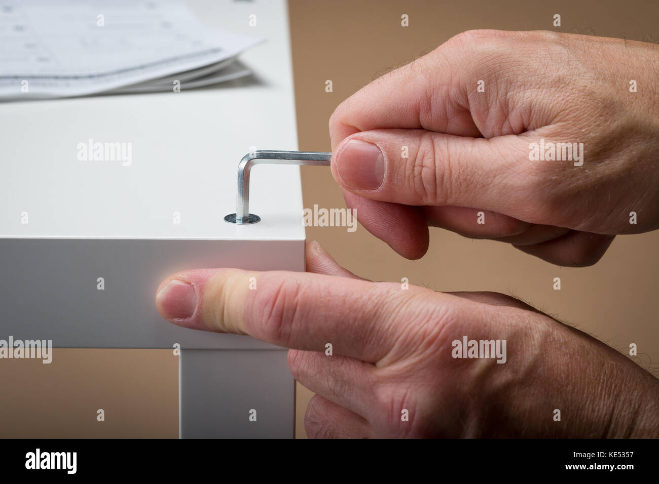 A man building flat pack furniture using an allen Key with the building instructions in the background - Stock Image