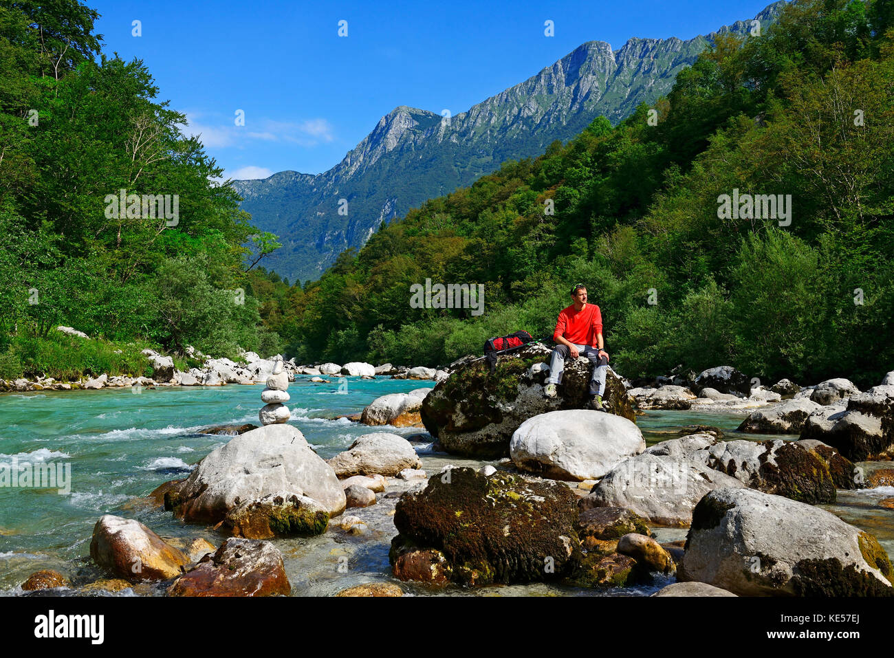 Hikers resting at the river Soca, near Kobarid, Slovenia Stock Photo