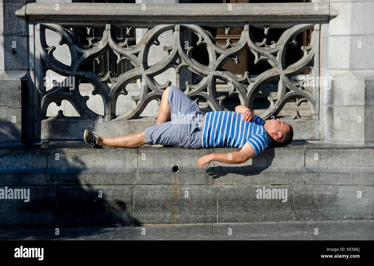 Brussels, Belgium. Grand Place: man asleep - Stock Image