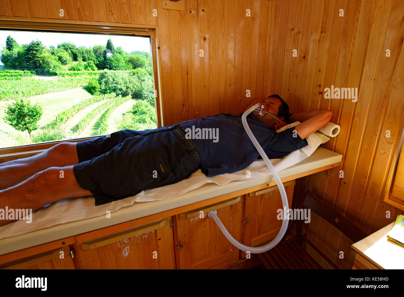 Man lying on a couch, bee therapy, api tourism, Dobrovo, Brda, Slovenia - Stock Image