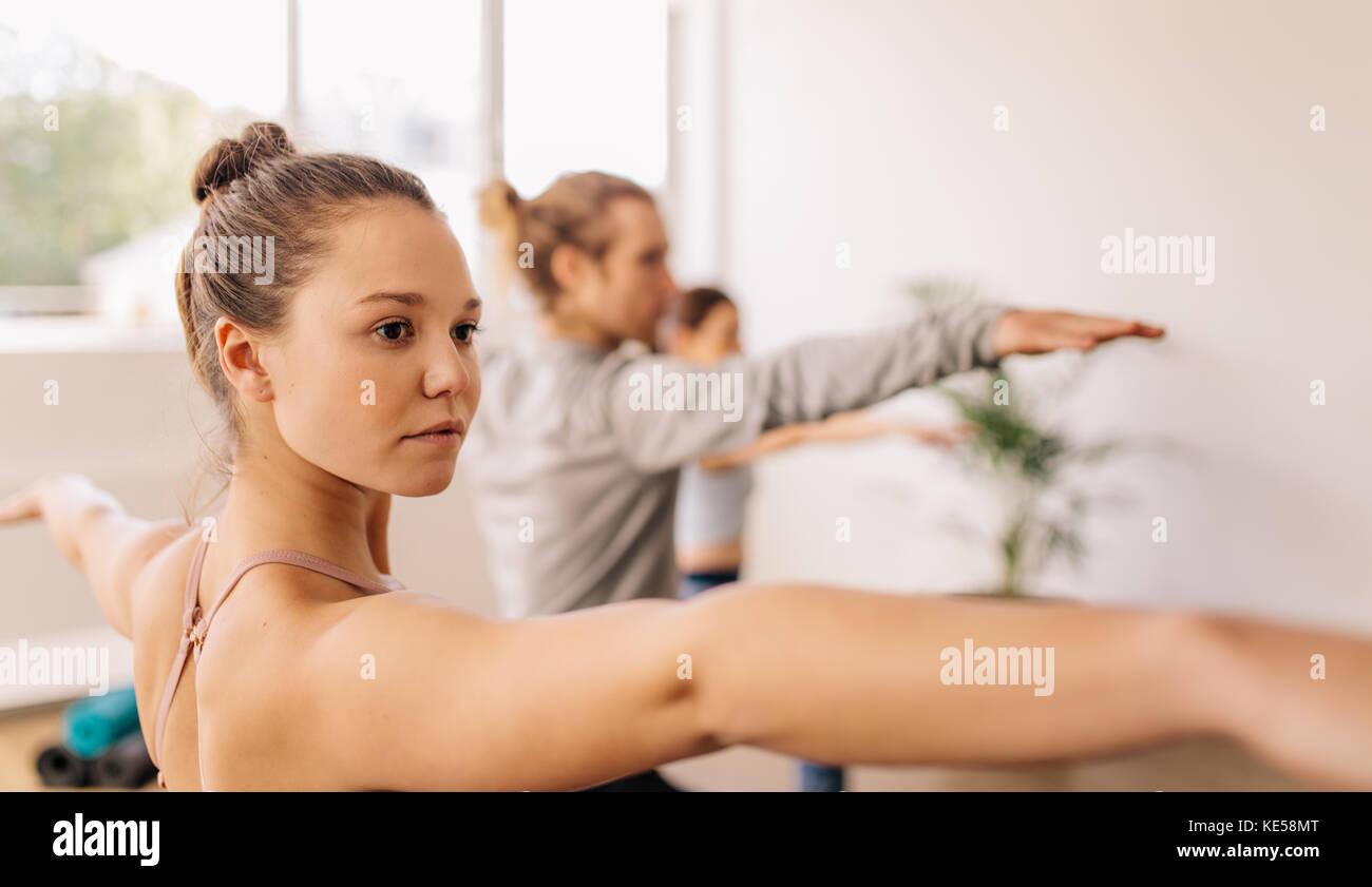 Fitness people doing yoga. Women exercising at yoga class. Virabhadrasana pose. - Stock Image