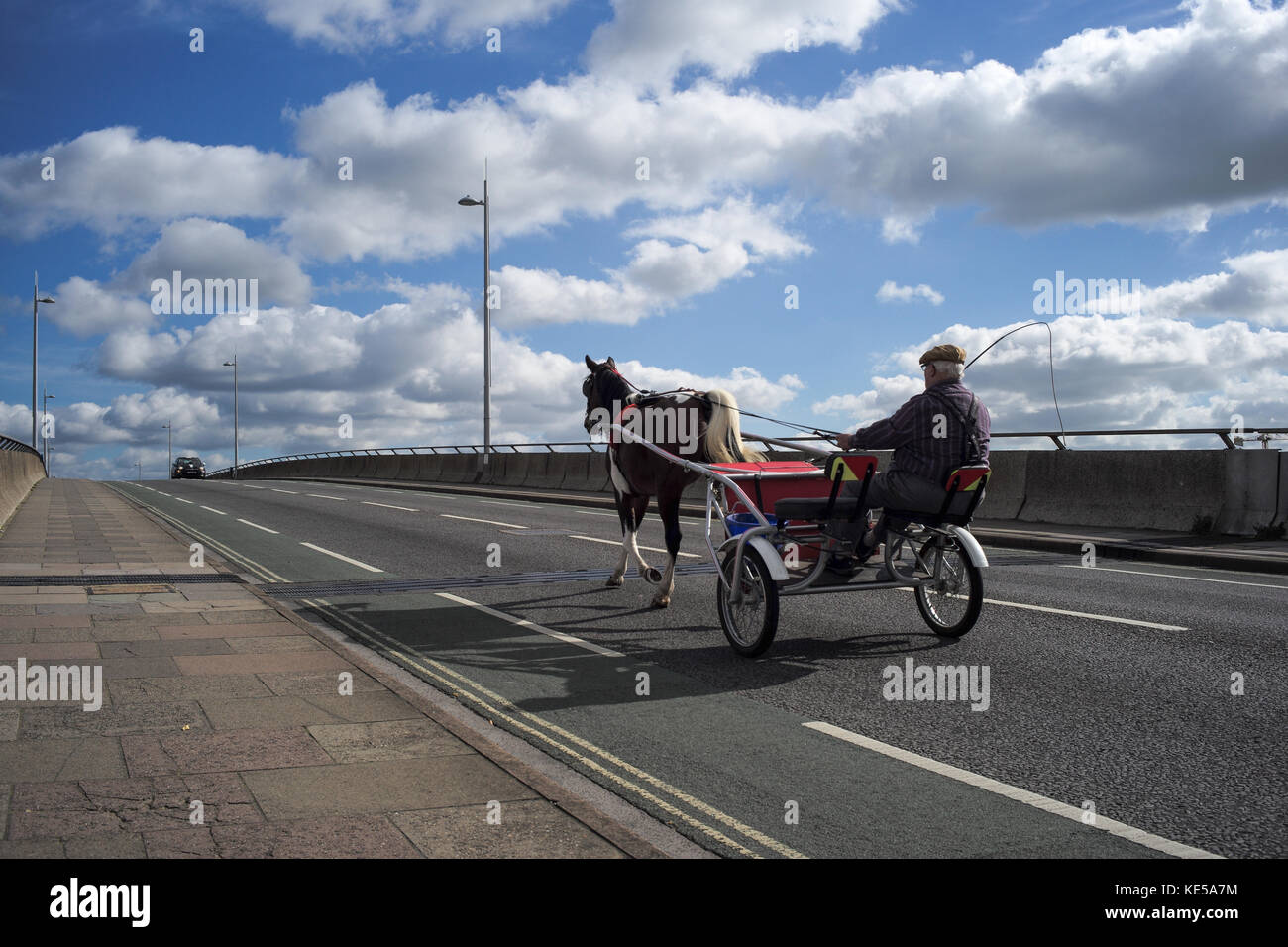 An old man using a horse and trap as transport riding over Itchen toll bridge in Southampton England. - Stock Image