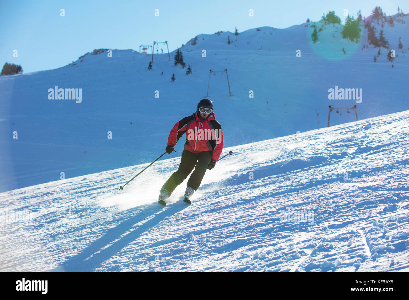 Skier skiing downhill in high mountains against sunset - Stock Image