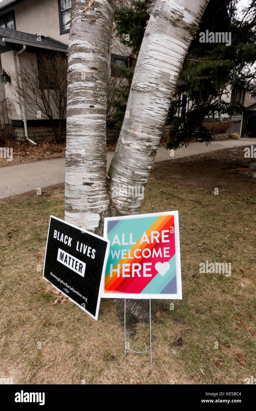 Black Lives Matter and 'All are Welcome Here' signs under a birch tree in a neighborhood yard. St Paul Minnesota - Stock Image